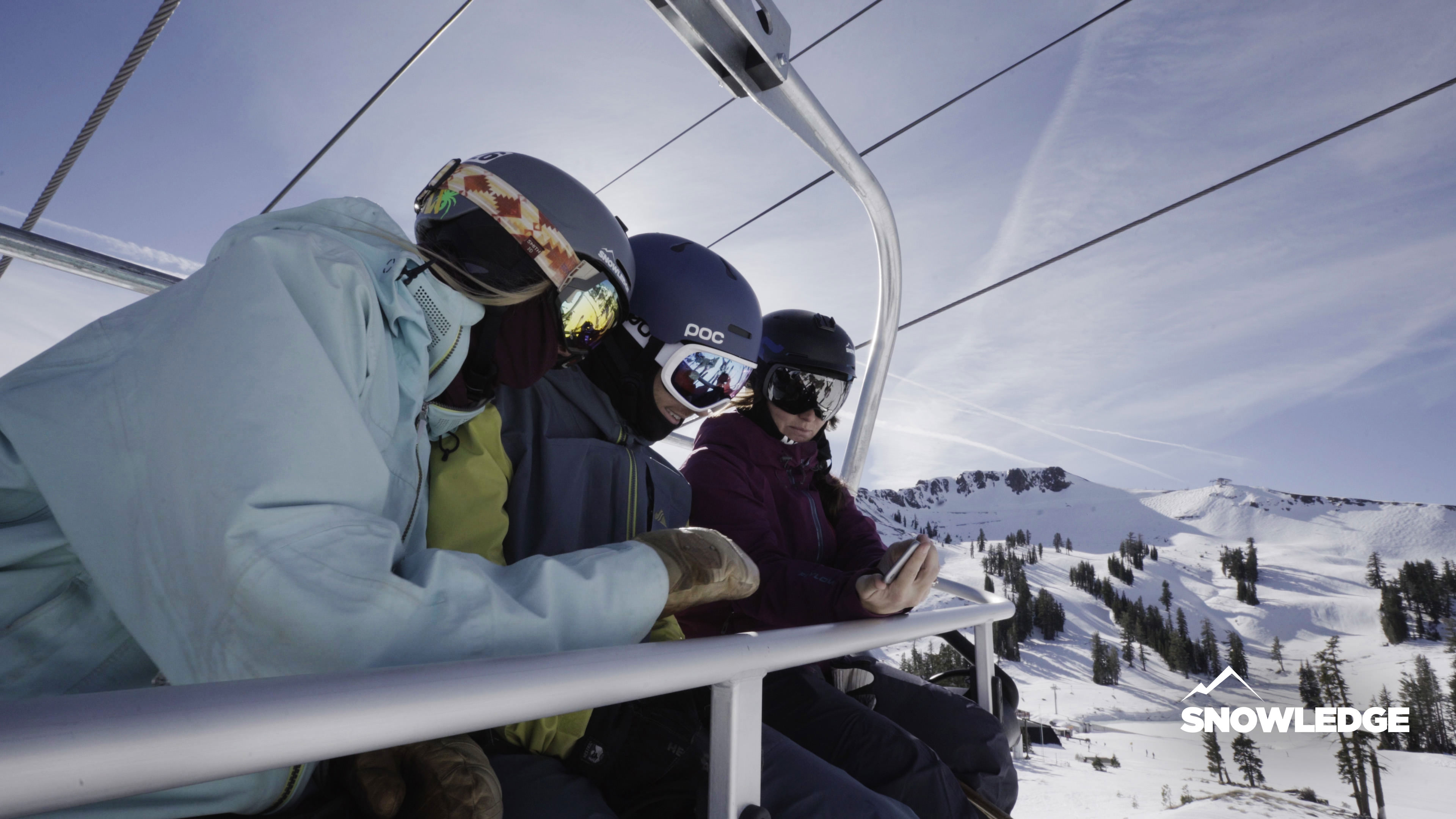 Skiers looking at a phone while on a lift